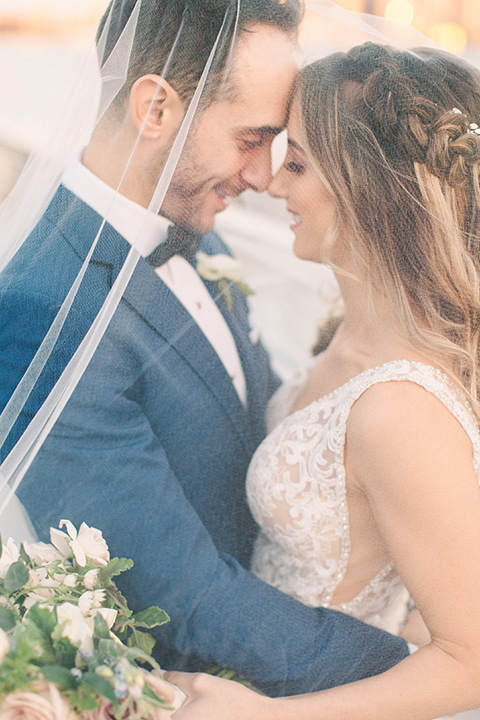 bride in an ivory lace gown with a modern geometric pattern and a v neckline, the groom wore a cobalt blue suit with a black bowtie under veil