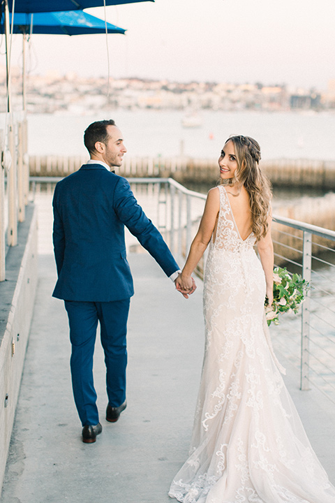 bride in an ivory lace gown with a modern geometric pattern and a v neckline, the groom wore a cobalt blue suit with a black bowtie walking