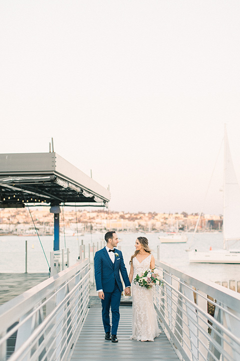 bride in an ivory lace gown with a modern geometric pattern and a v neckline, the groom wore a cobalt blue suit with a black bowtie walking towards camera
