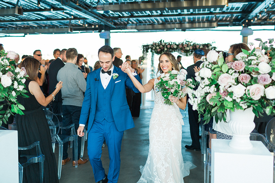 bride in an ivory lace gown with a modern geometric pattern and a v neckline, the groom wore a cobalt blue suit with a black bowtie walking out of ceremony