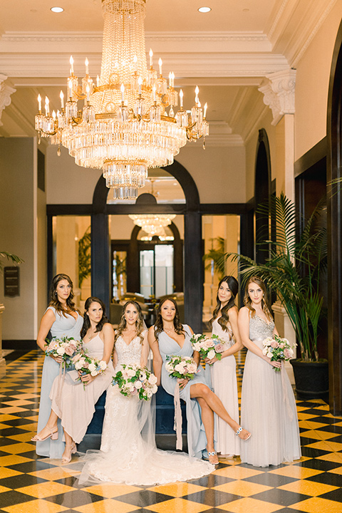 bride in an ivory lace gown with a modern geometric pattern and a v neckline and the bridesmaids in pastel gowns