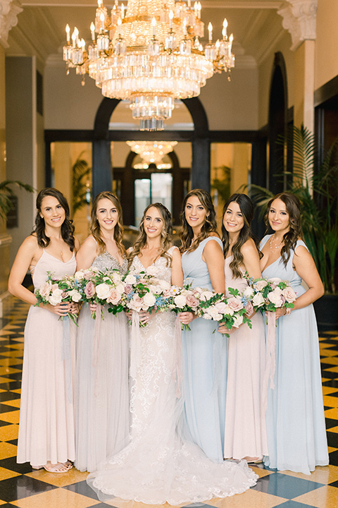bride in an ivory lace gown with a modern geometric pattern and a v neckline and bridesmaids in pastel dresses