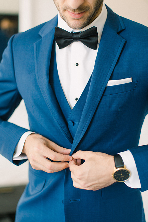 groom close up with a cobalt suit with a black bow tie