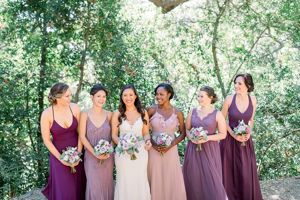 bride in a white lace formfitting gown with thin straps, bridesmaids in mauve and pink gowns