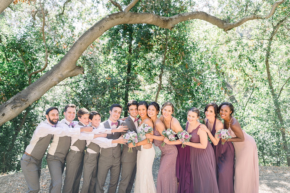 bride in a white lace formfitting gown with thin straps, the groom in a café brown suit with a purple bow tie, the bridesmaids wore mauve and pink dresses and groomsmen wore a laid back look with café brown pants and vest with purple bow ties