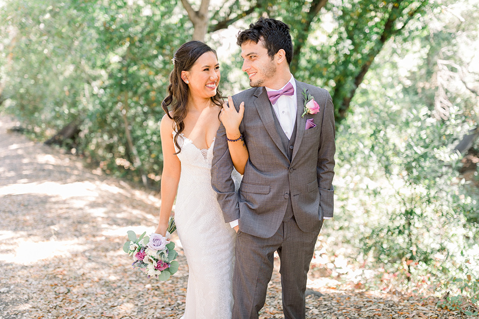 bride in a white lace formfitting gown with thin straps, the groom in a café brown suit with a purple bow tie locking arms