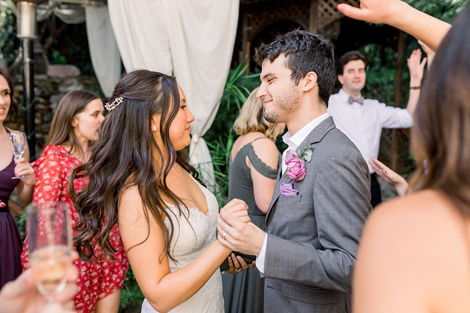 bride in a white lace formfitting gown with thin straps, the groom in a café brown suit with a purple bow tie dancing at their reception