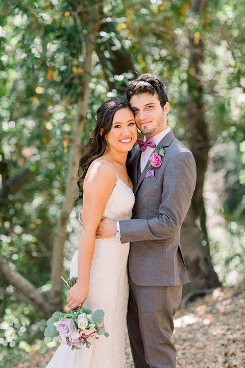 bride in a white gown with lace and thin straps and the groom in a café brown suit with a purple bow tie hugging