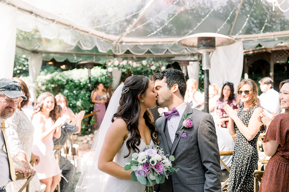 bride in a white lace formfitting gown with thin straps, the groom in a café brown suit with a purple bow tie kissing at ceremony