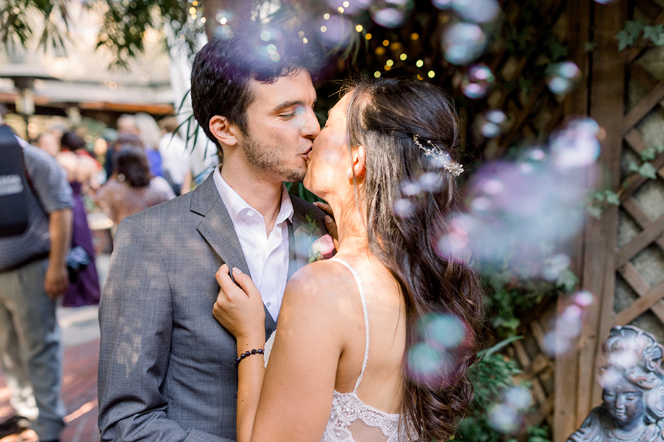 bride in a white lace formfitting gown with thin straps, the groom in a café brown suit with a purple bow tie kissing with bubbles