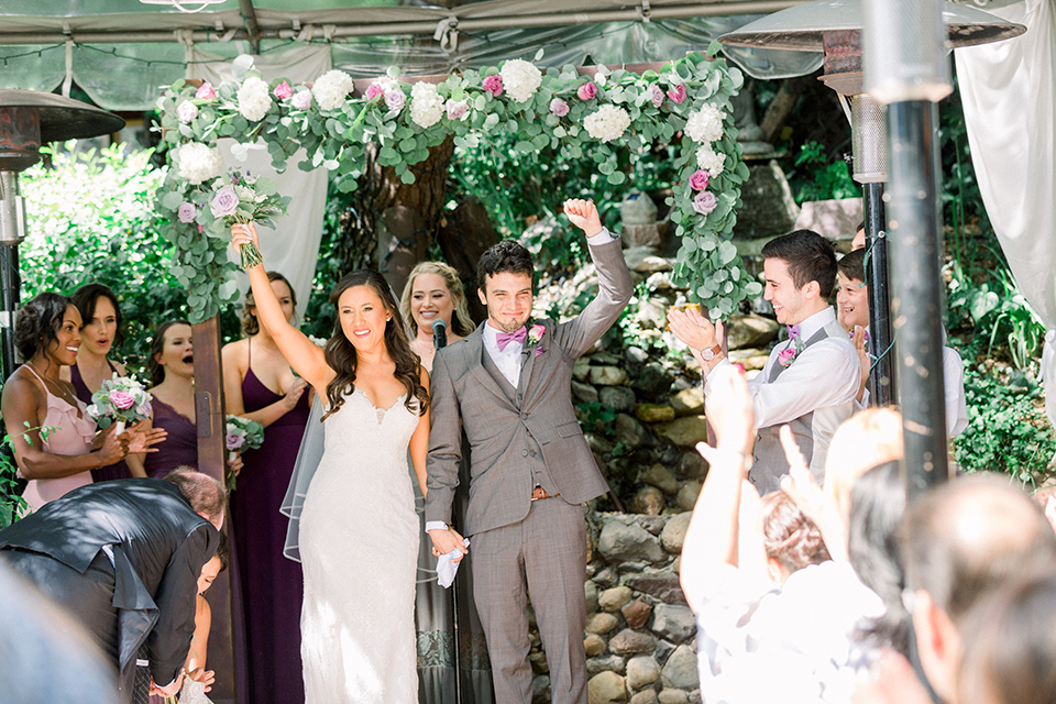 bride in a white lace formfitting gown with thin straps, the groom in a café brown suit with a purple bow tie walking down the aisle