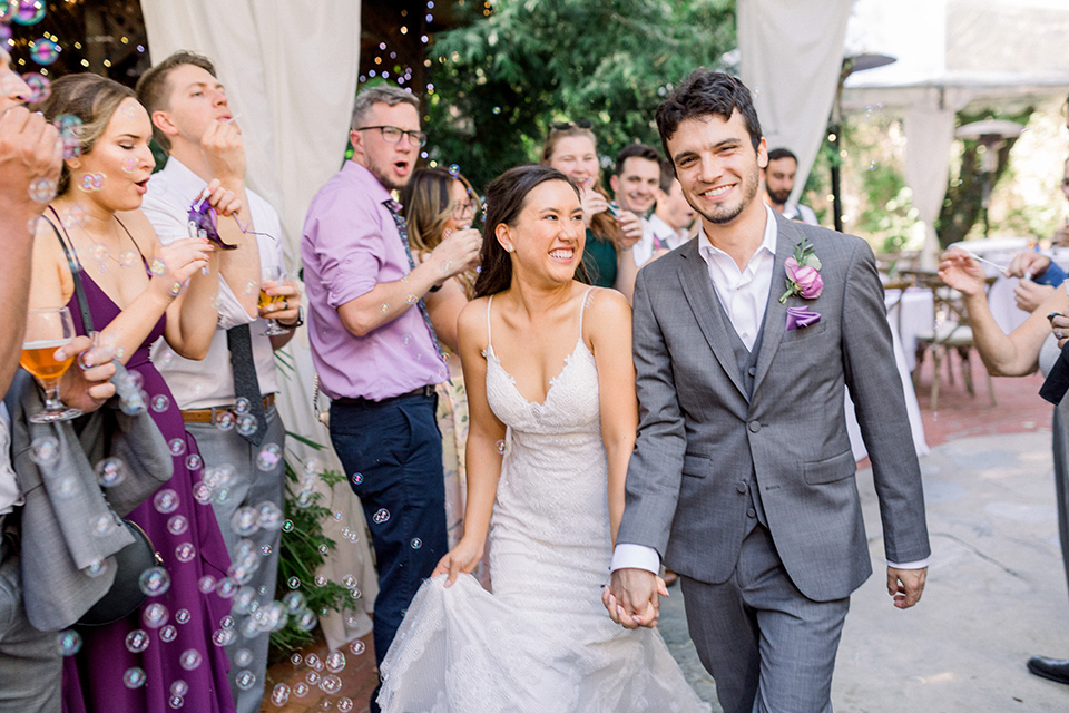 bride in a white lace formfitting gown with thin straps, the groom in a café brown suit with a purple bow tie walking down the aisle holding hands