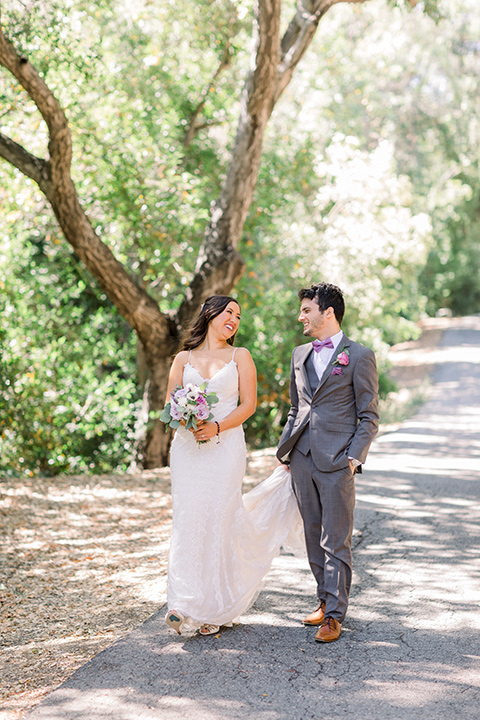 bride in a white lace gown with thin straps and veil and groom in a café brown suit, walking together
