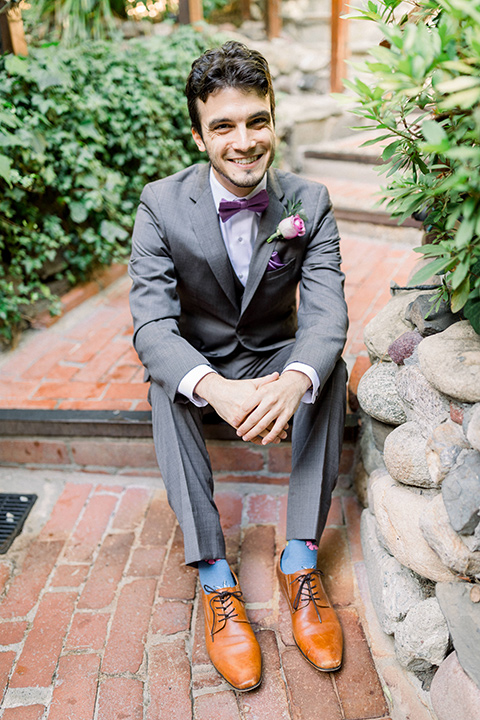 groom in a café brown suit with a purple bow tie sitting on steps