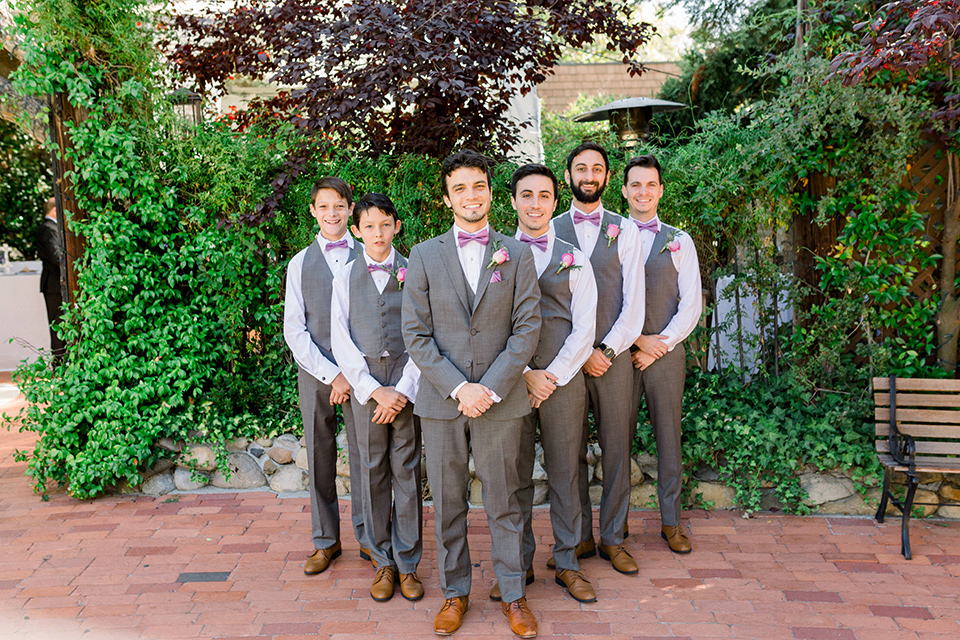 groom in a café brown suit with a purple bow tie, the groomsmen in café brown pants and vests