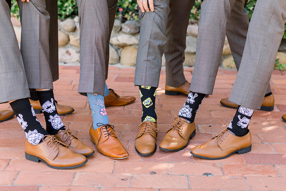 groom in a café brown suit with a purple bow tie, the groomsmen in café brown pants and vests wearing fun socks