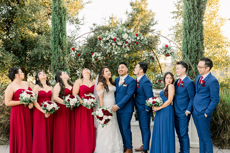 bride in a Spanish style lace gown with off the shoulder detailing, the groom in a cobalt suit with a pink long tie, the groomsmen in cobalt suits with red long ties, and bridesmaids in red dresses