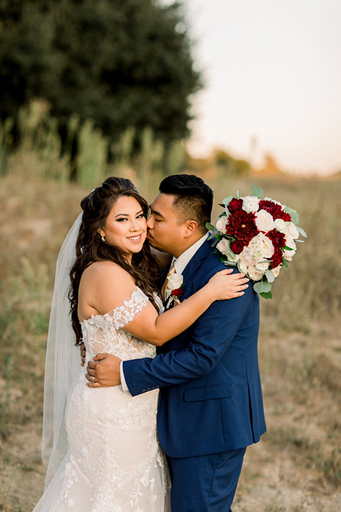 bride in a Spanish style lace gown and the groom in a cobalt suit with a pink tie, they embrace