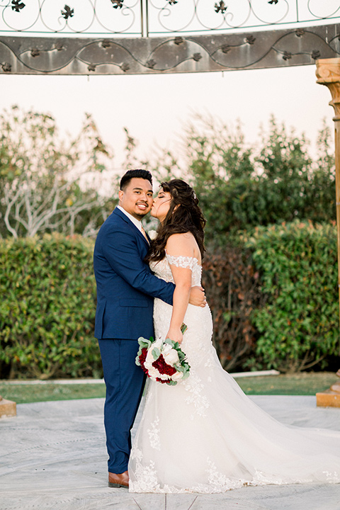 bride in a Spanish style lace gown and the groom in a cobalt blue suit with a pink suit