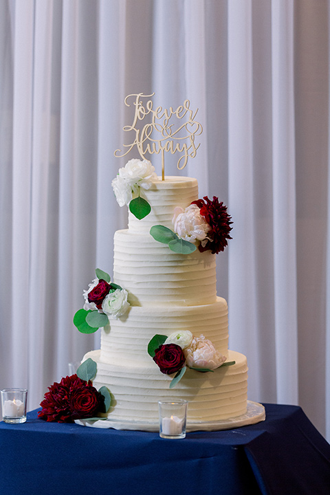 white cake with red and white flowers