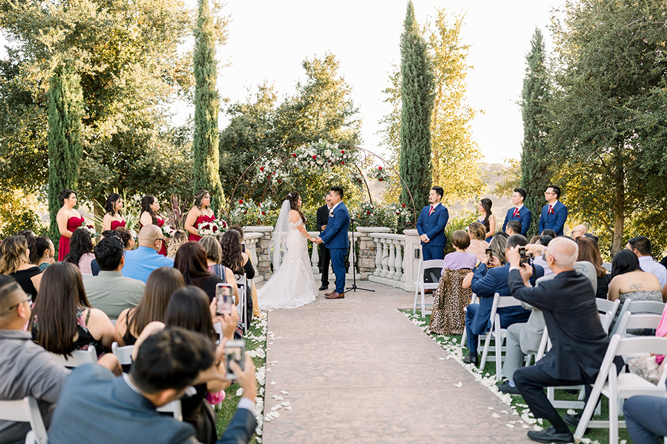 bride in a Spanish style lace gown with off the shoulder detailing, the groom in a cobalt suit with a pink long tie, the groomsmen in cobalt suits with red long ties, and bridesmaids in red dresses at ceremony