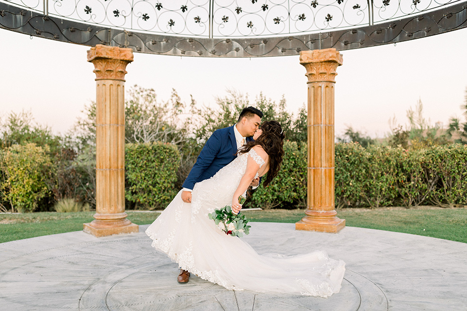 bride in a Spanish style lace gown with off the shoulder detailing, the groom in a cobalt suit with a pink long tie dipping bride