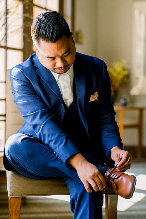 groom in a cobalt blue suit with a brown shoes