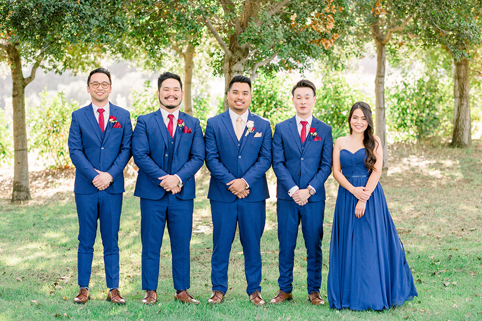 the groomsmen in cobalt suits with red long ties and a groomswoman in a cobalt dress