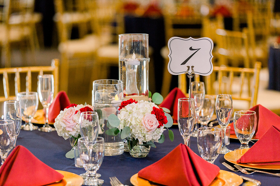 blue table linens with red napkins with gold flatware