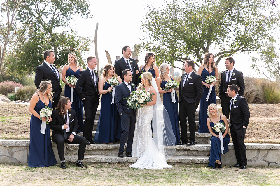 bride in a white lace gown and the groom in a navy shawl lapel tuxedo and blow tie, bridesmaids in navy gowns and groomsmen in black tuxedos