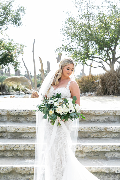 bride in a white lace gown and long veil