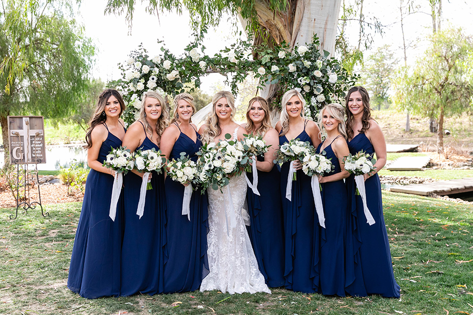 bride in a white lace gown and the bridesmaids in navy long gowns