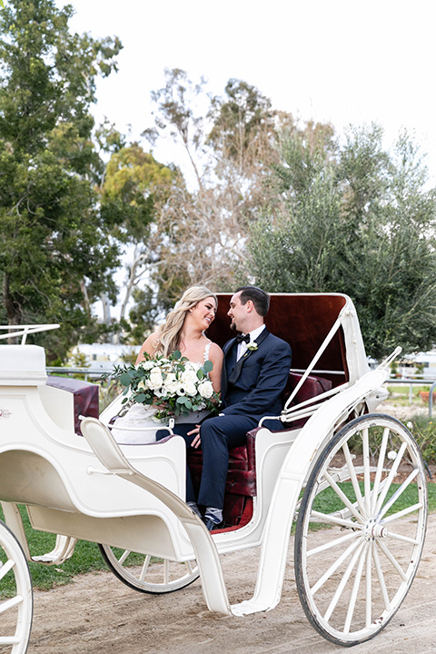 bride in a lace gown and long veil, groom in a navy shawl lapel tuxedo with a black bow tie in horse drawn carriage