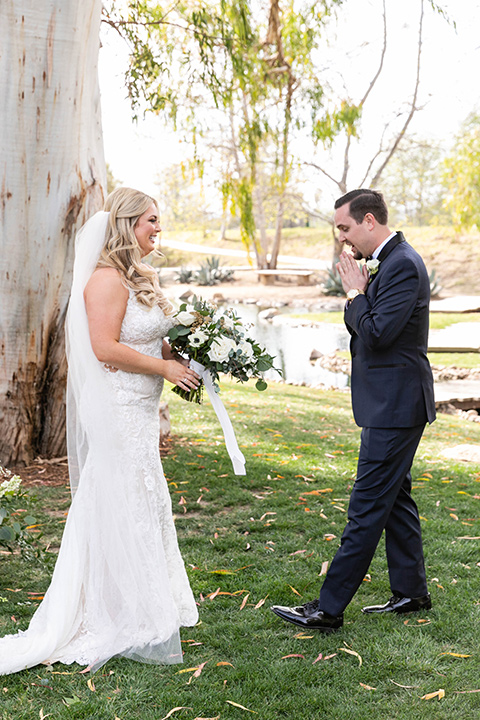 bride in a lace gown and long veil, groom in a navy shawl lapel tuxedo with a black bow tie – first look