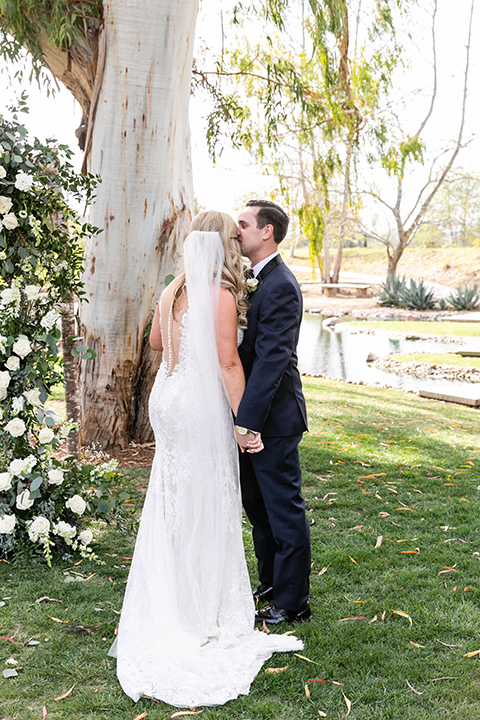bride in a white long lace gown with a long veil and the groom in a navy shawl lapel tuxedo