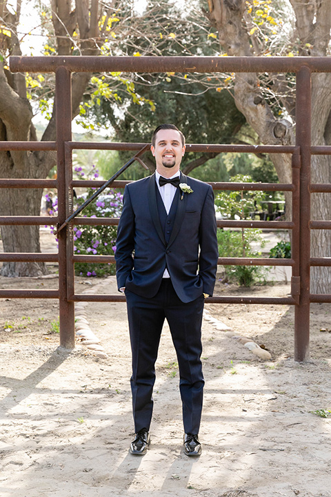 groom in a navy shawl lapel tuxedo with a black bow tie