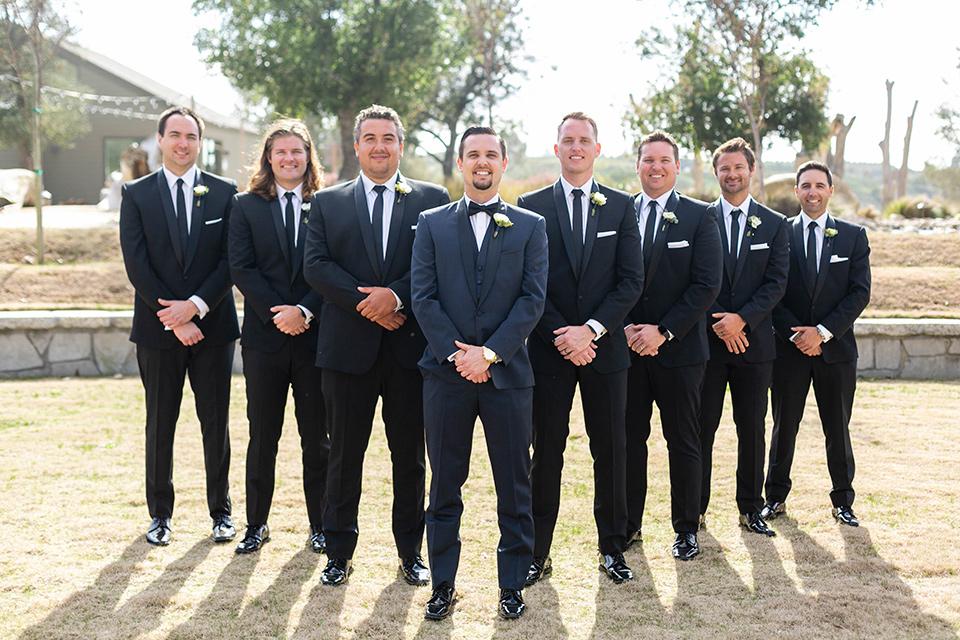 groom in a navy shawl lapel tuxedo and groomsmen in black tuxedos