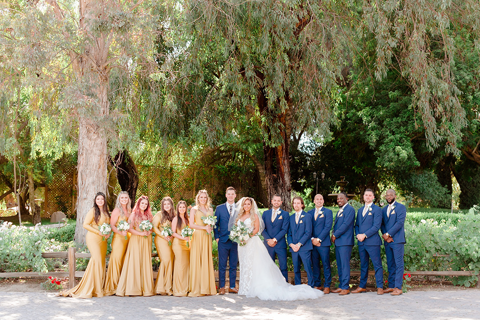 bride in a white lace gown with a long train and veil, groom in a cobalt blue suit with a blue floral long tie, the bridesmaids in a gold ballgowns and groomsmen in cobalt blue suit with blue floral bow ties