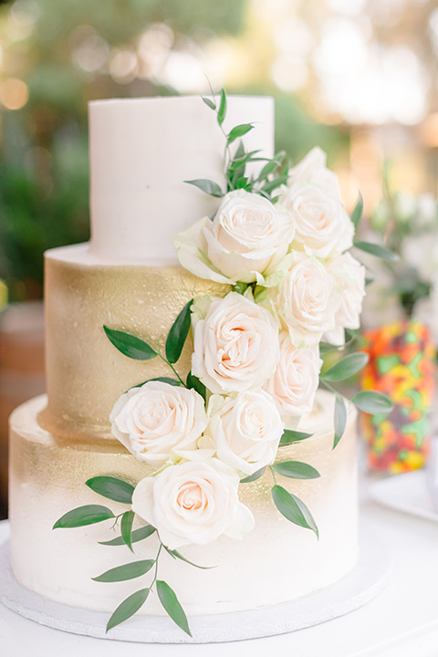 white and gold cake with white florals flowers