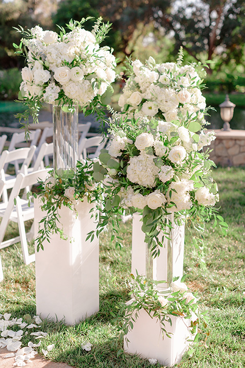 white floral décor on the ceremony arch