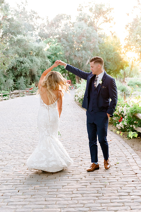 bride in a white lace gown with a long train and veil, groom in a cobalt blue suit with a blue floral long tie dancing