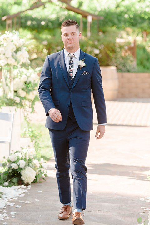 groom in a cobalt blue suit with a blue floral long tie walking down the aisle