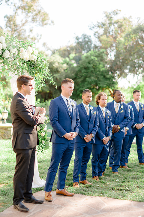 groom in a cobalt blue suit with a blue floral long tie and groomsmen in blue suits with floral bow ties