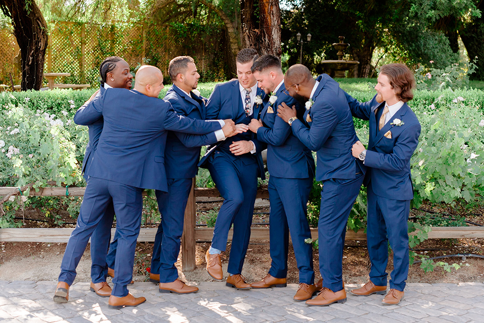 groom in a cobalt blue suit with a blue floral long tie and groomsmen in cobalt blue suit with blue floral bow ties