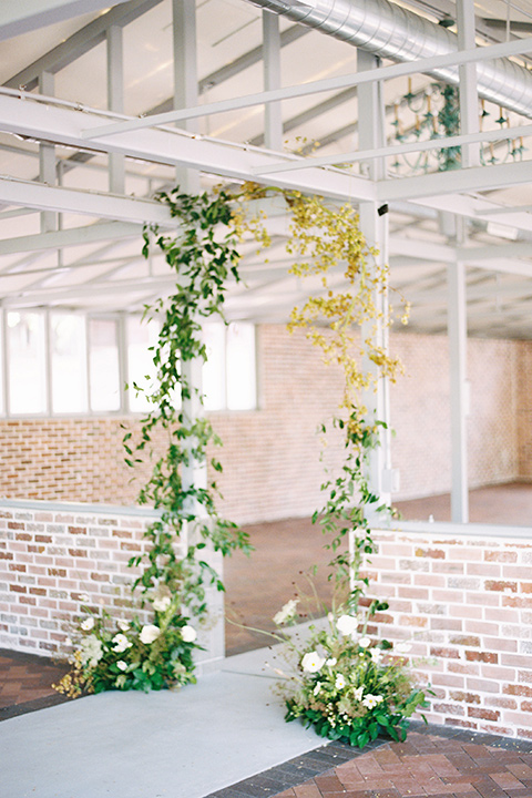 ceremony arch with green and yellow flowers