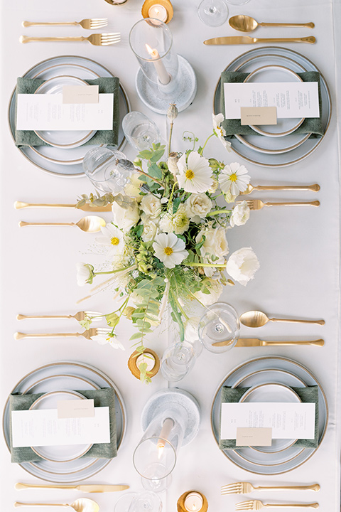 white linens with silver plate chargers and gold flatware