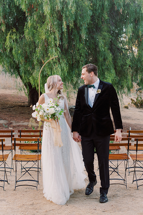 bride in a formfitting gown with long cathedral veil and the groom in a black velvet tuxedo