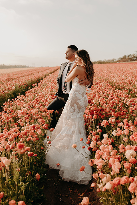 bride in a tulle ballgown and the groom in an asphalt grey michael kors suit in the flower fields in temecula