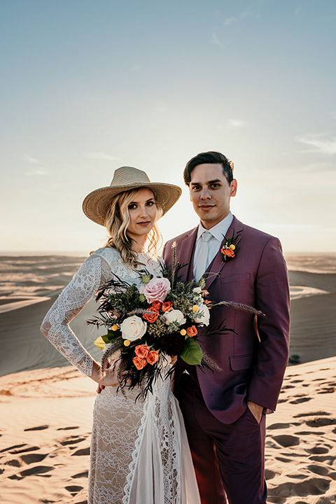 bride in a lace gown with long sleeves and a wide brimmed hat and the groom in a rose pink suit with a white long tie