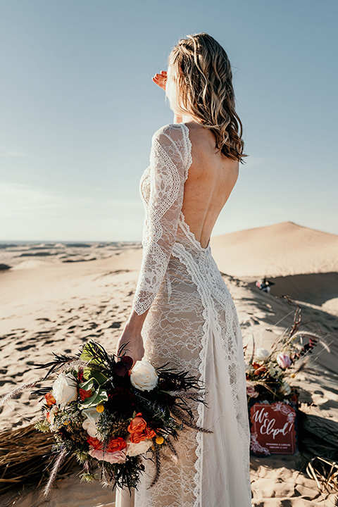 bride in a lace gown with long sleeves and a wide brimmed hat